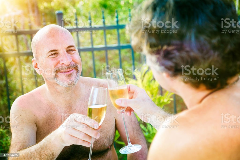 Gay mature nudist men toasting outside stock photo