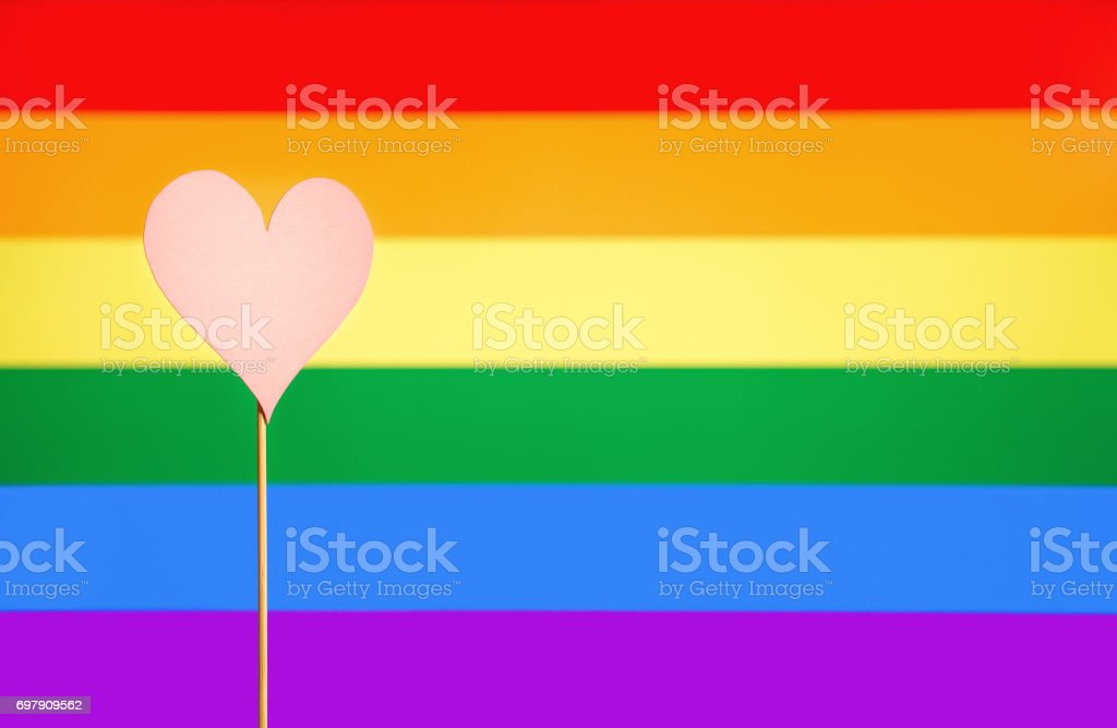 Gay pride and LGBT background. Rainbow flag design template with copy space. Heart cut from cardboard paper on wooden stick. Sexual minority, homosexuality and equal rights. Handmade love symbol. stock photo