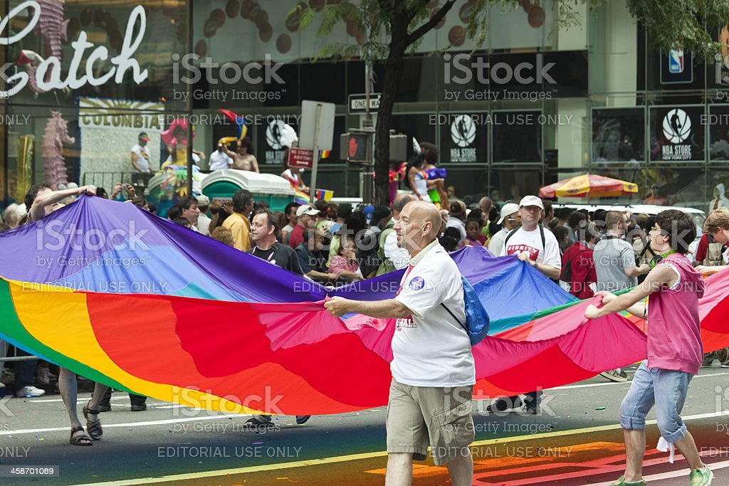Gay Pride Parade Goers Holding Large Rainbow Flag stock photo