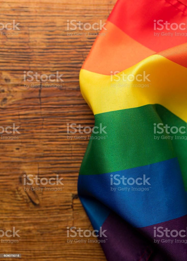 Gay pride rainbow flag on a wooden background stock photo