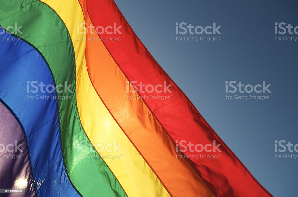 Gay Pride Rainbow Flag Waving in Sun against Blue Sky stock photo