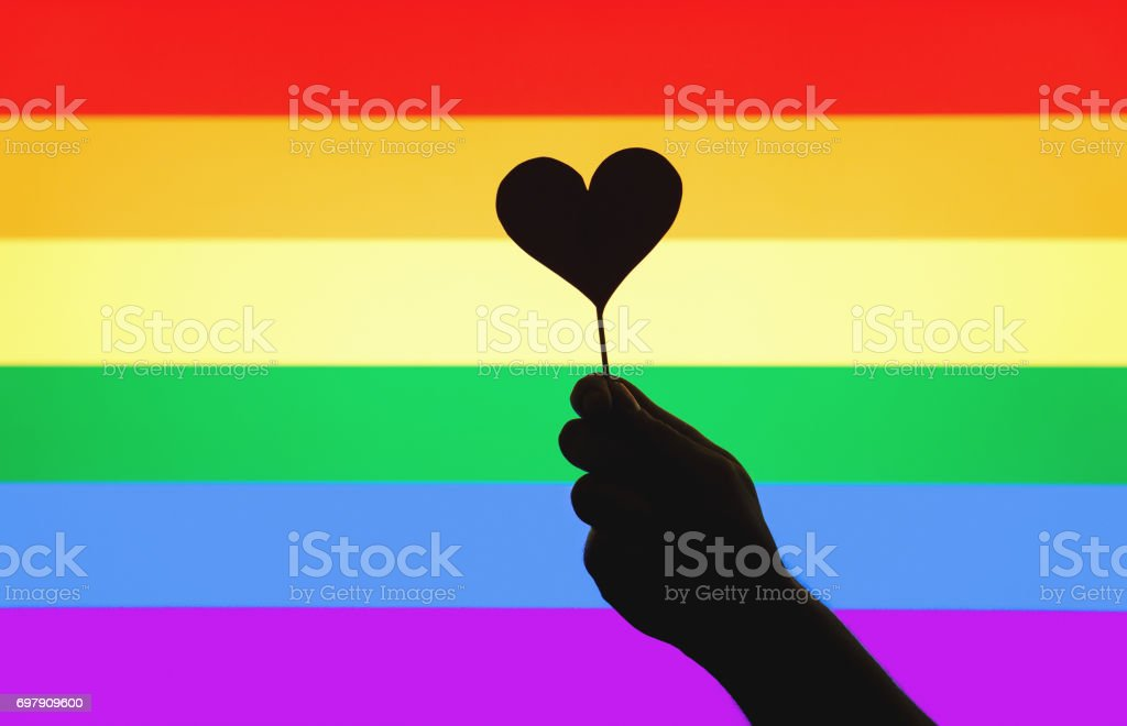 LGBT, gay pride, sexual minority, homosexuality and equal rights concept. Silhouette hand holding cardboard heart on a wooden stick against rainbow flag. Person showing little love symbol and sign. stock photo
