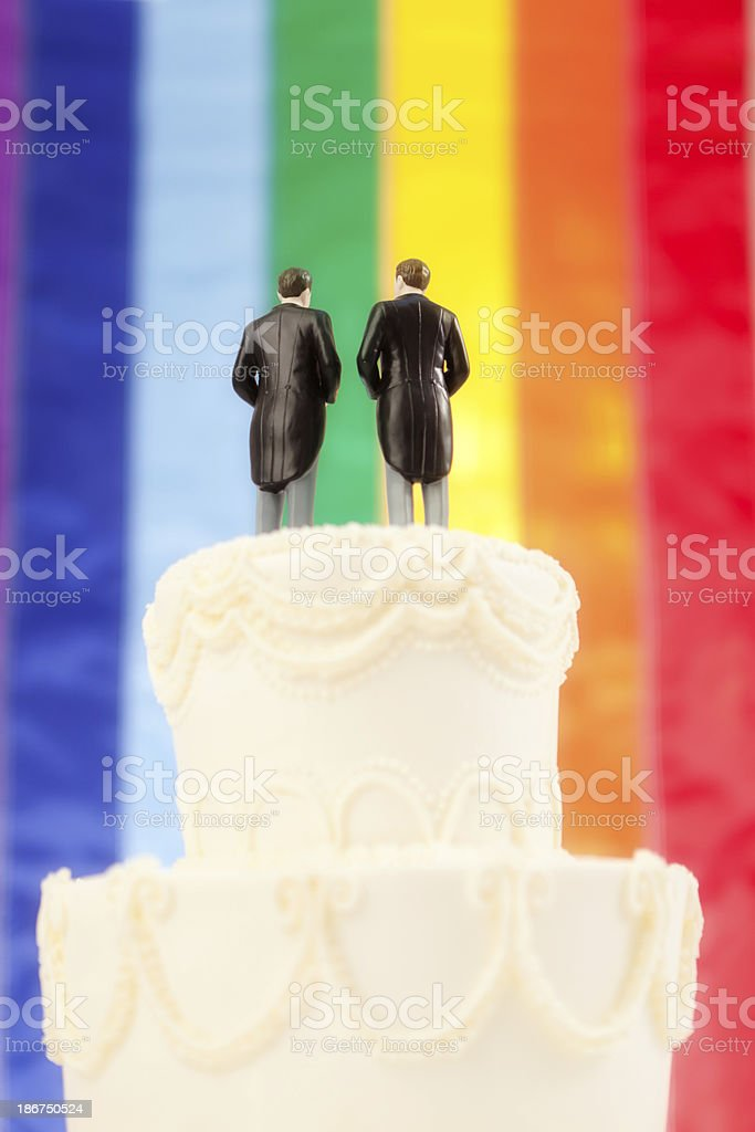 Gay Wedding Cake, Two Men Topper with Rainbow Flag Background royalty-free stock photo