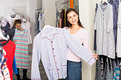Gay woman choosing pajamas top for man in shop