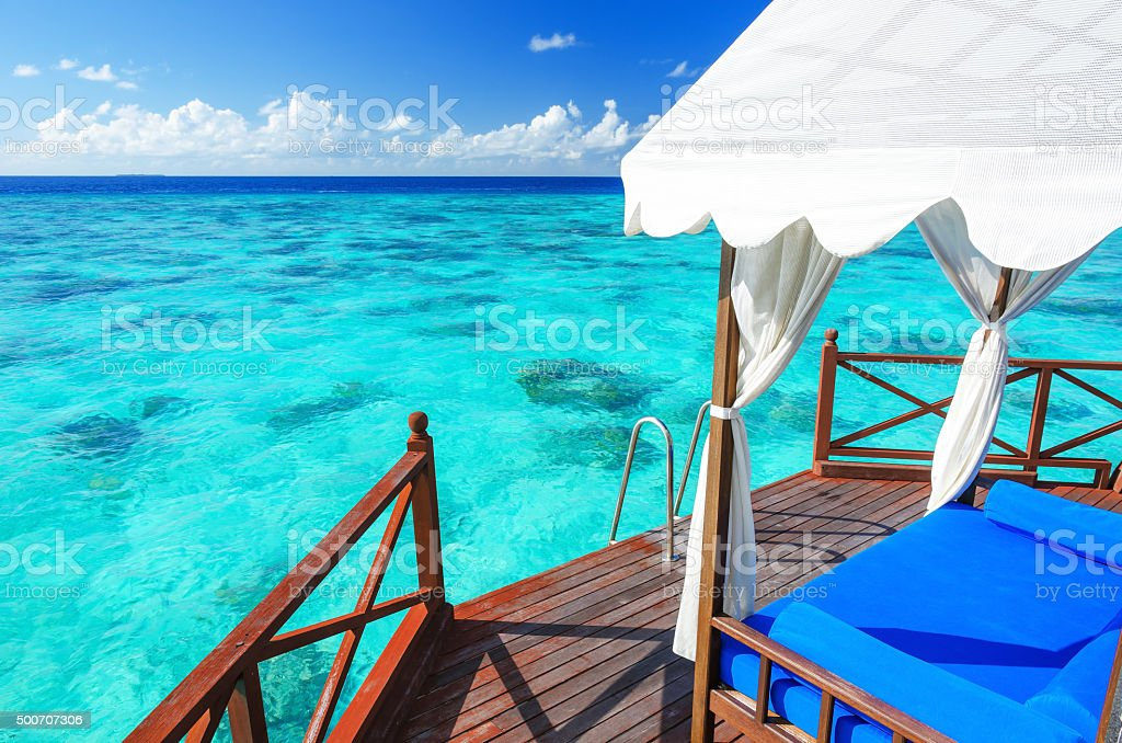 Gazebo at wooden balcony overlooking green tropical lagoon stock photo