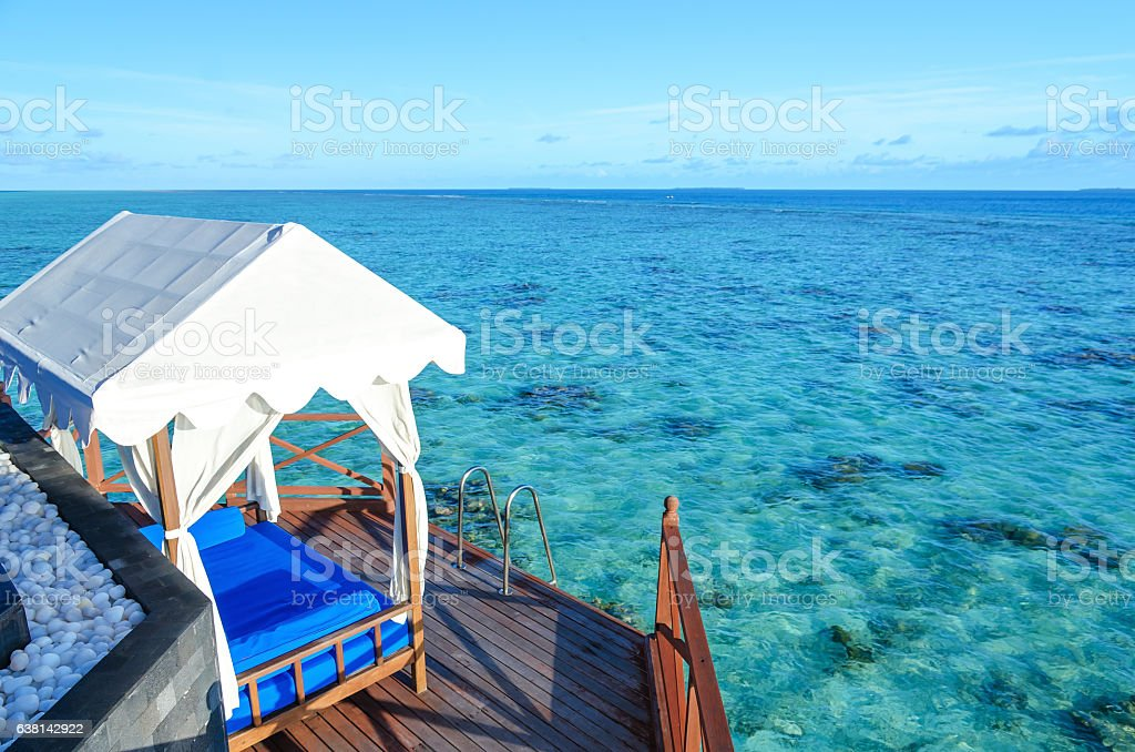 Gazebo at wooden balcony overlooking tropical sea stock photo