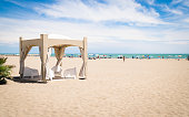 Gazebo with white chairs on the beach.