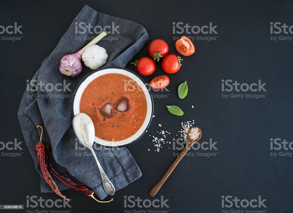 Gazpacho soup in rustic metal bowl with fresh tomatoes, green stock photo