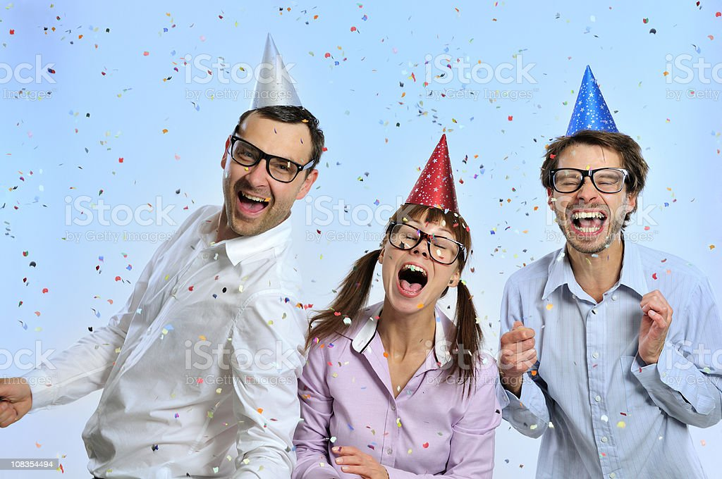 Geek group with party hats on head, confetti, toothy smiling stock photo