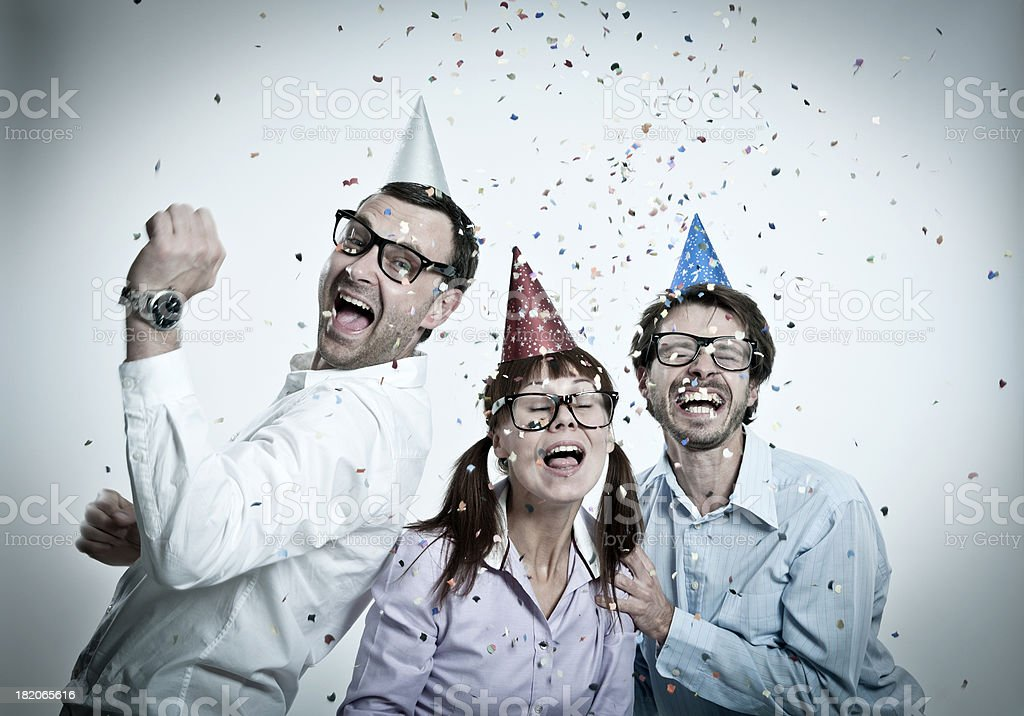 Geek group with party hats on head, confetti, toothy smiling royalty-free stock photo