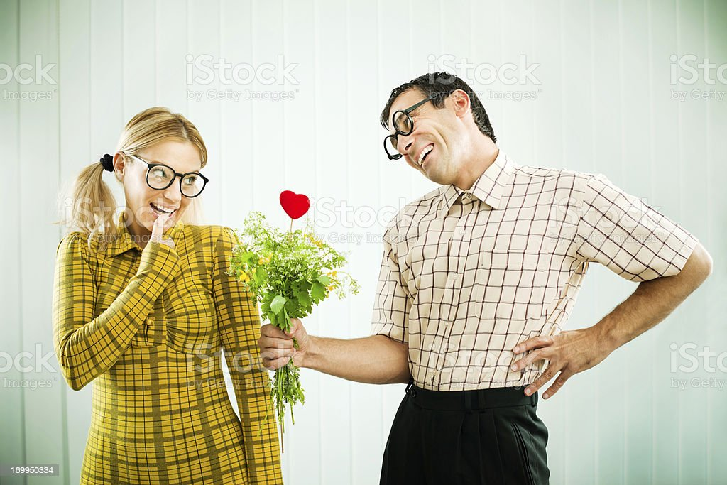 Geek man giving his girlfriend a Valentine present. stock photo