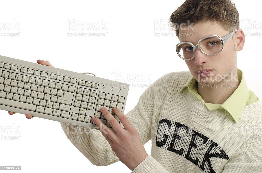 Geek playing video games with a keyboard, gamer wearing eyeglasses royalty-free stock photo