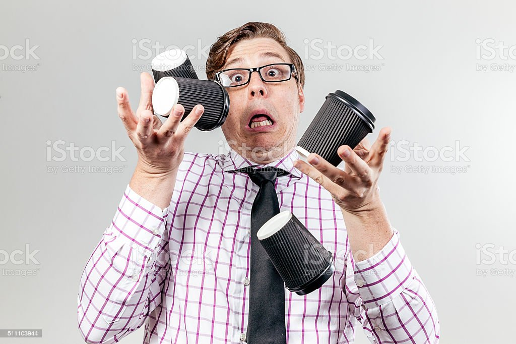 Geek spilling coffee cups everywhere stock photo