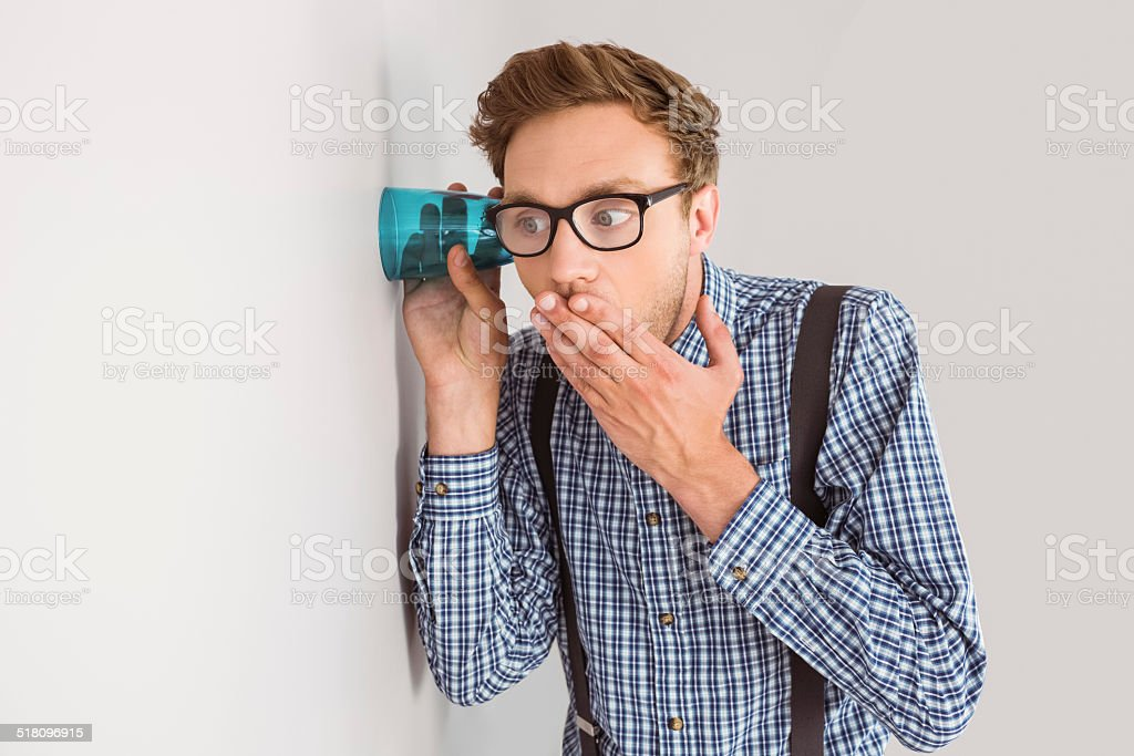 Geeky businessman eavesdropping with cup stock photo