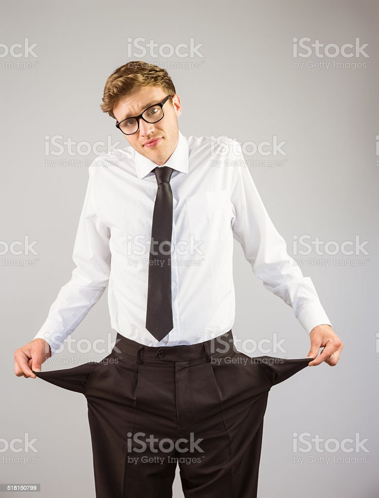 Geeky businessman showing his empty pockets stock photo