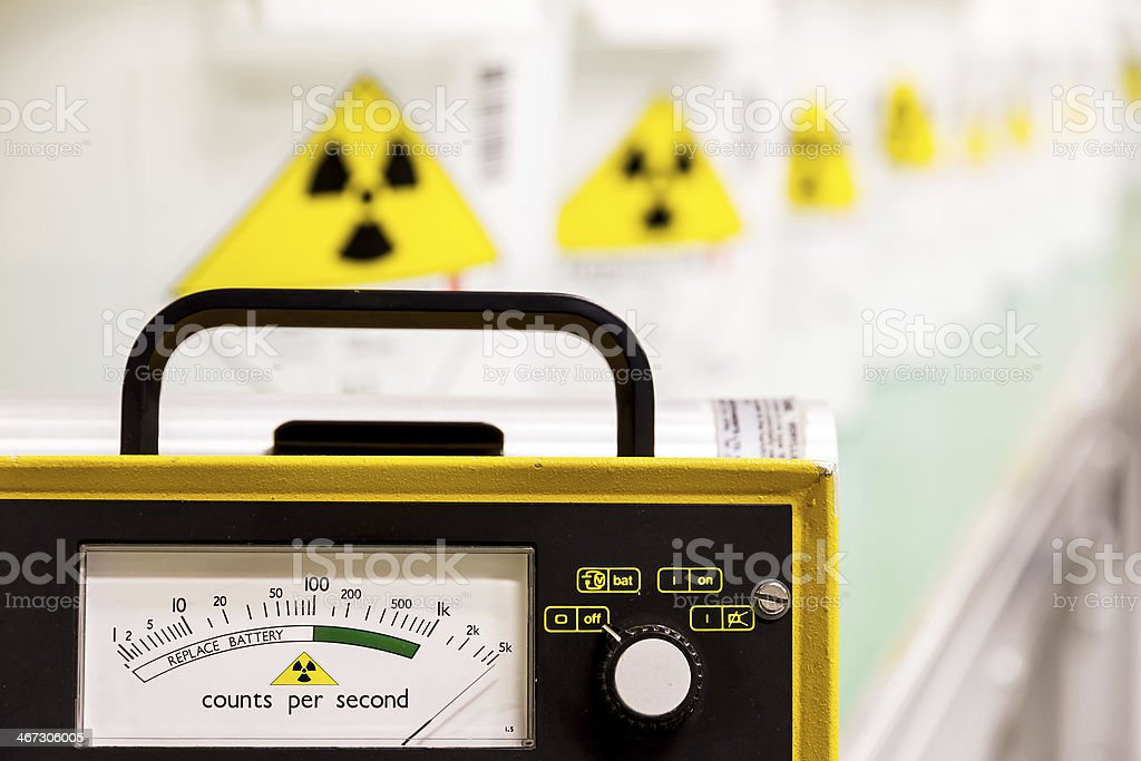 Geiger counter with yellow hazard signs in row fading behind stock photo
