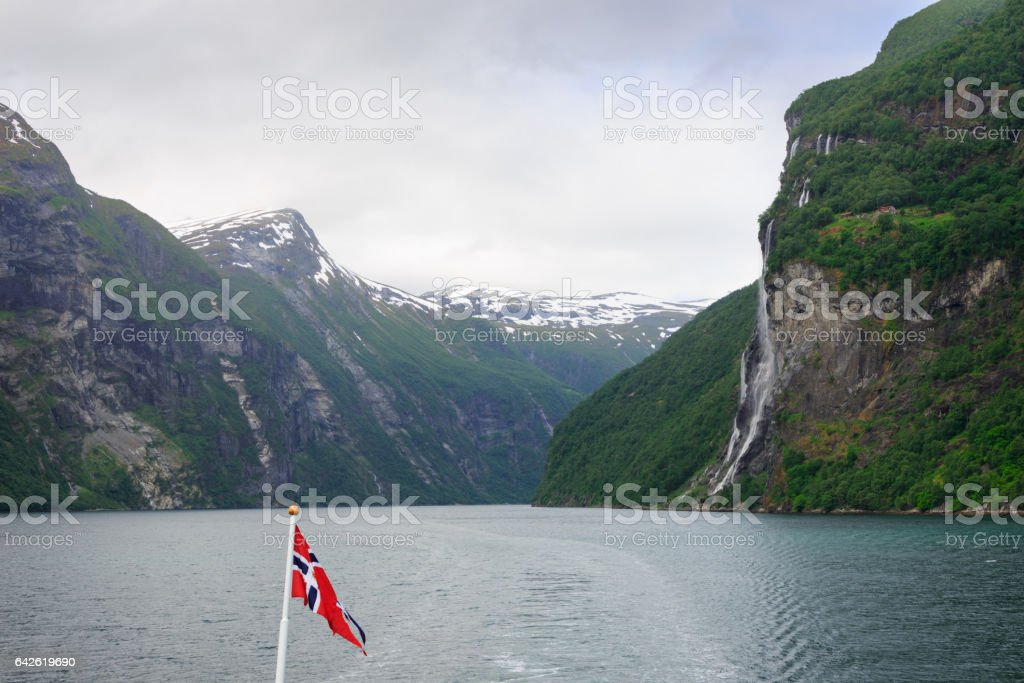Geirangerfjord with waterfall and Norwegian flag stock photo