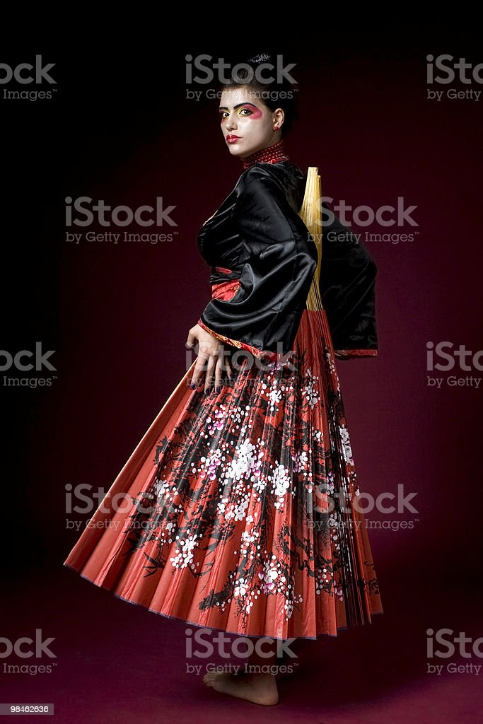 Geisha hiding behind a painted big fan stock photo