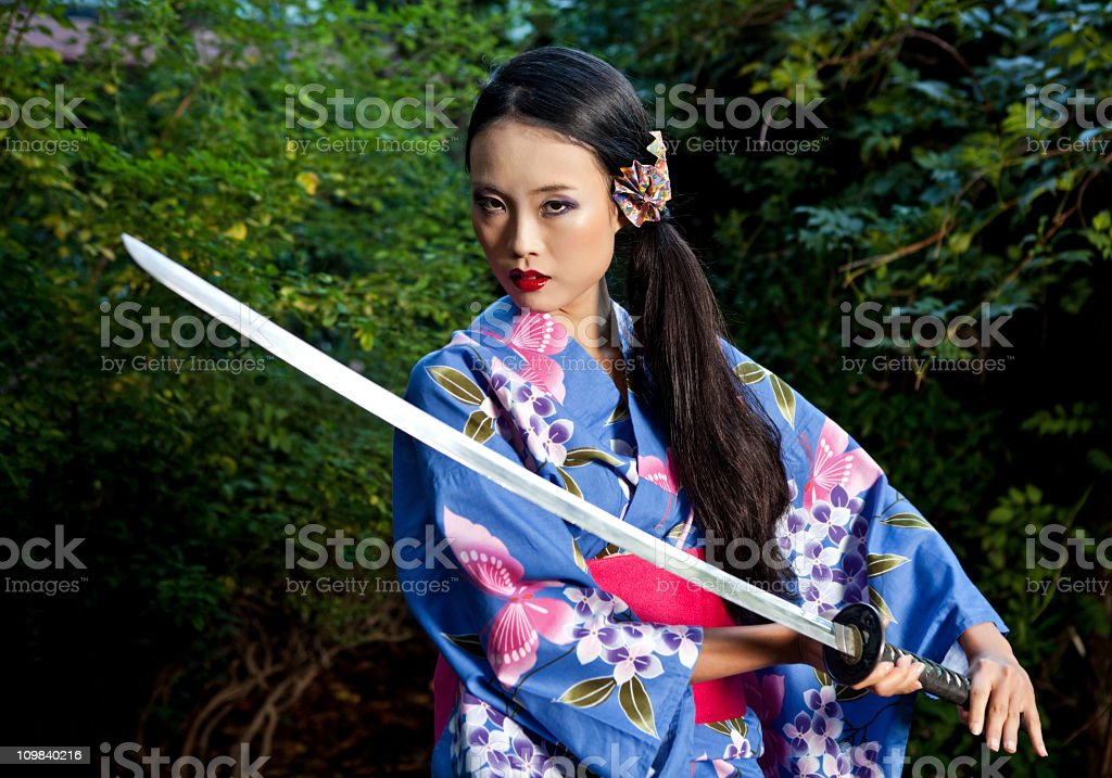 Geisha with red lipstick holding a katana stock photo