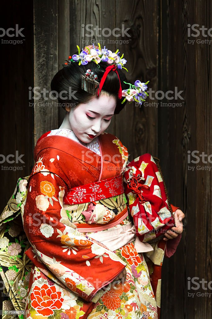 Geisha Women in Kimono Waiting in a Traditional Japanese Alleyway stock photo
