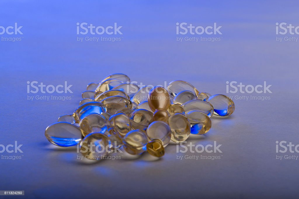 Gel capsules on the white background illuminated with blue lighting stock photo