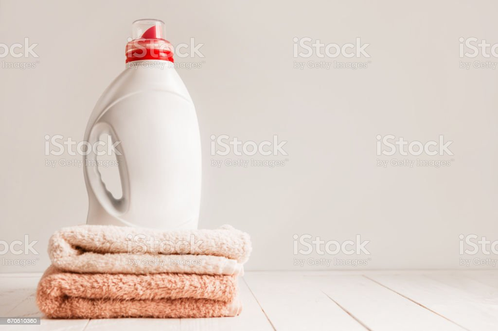 Gel for laundry washing in a white unnamed plastic bottle, standing on a fresh colored towels. Composition on white wooden shelf stock photo