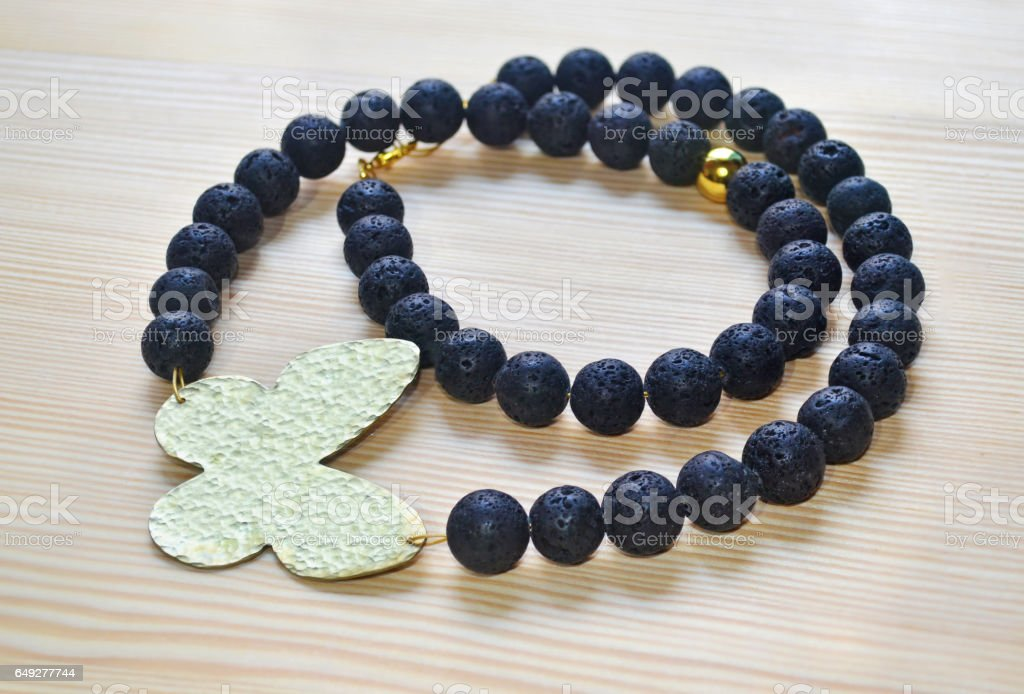 gemstone black lava necklace with gold butterfly stock photo