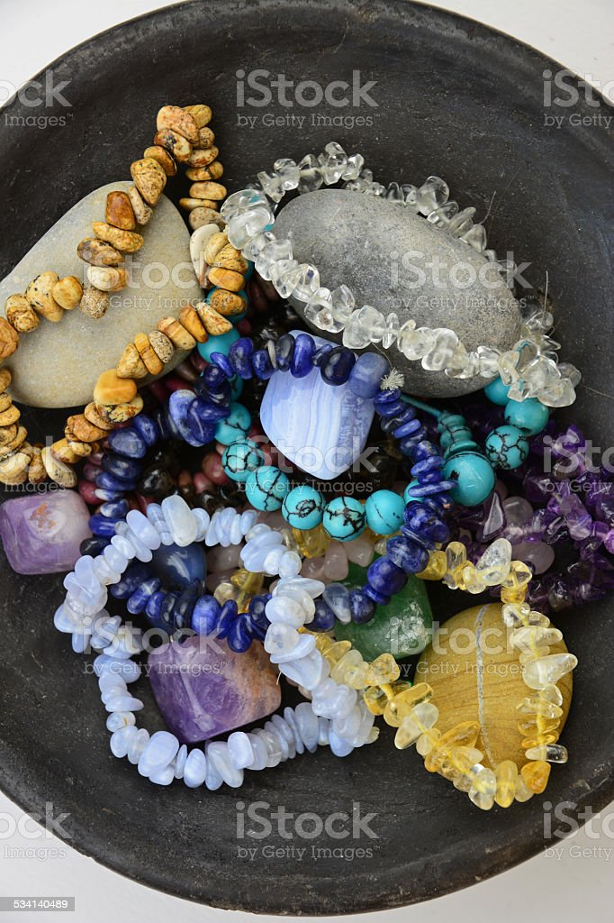 gemstones and crystals decorated in old earthenware dish on wood stock photo