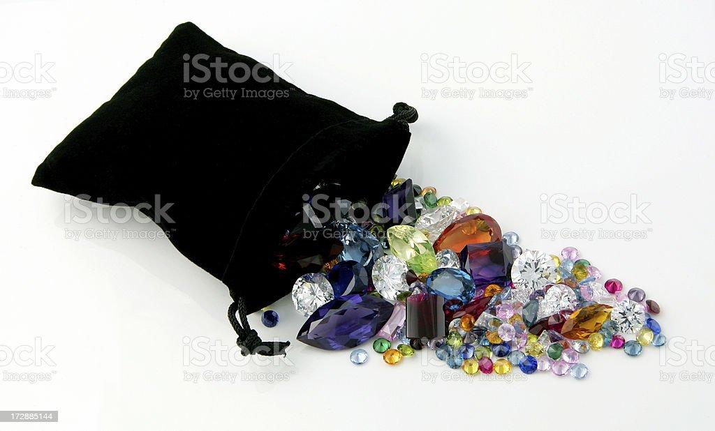 Gemstones spilling out of Black Velvet Bag stock photo