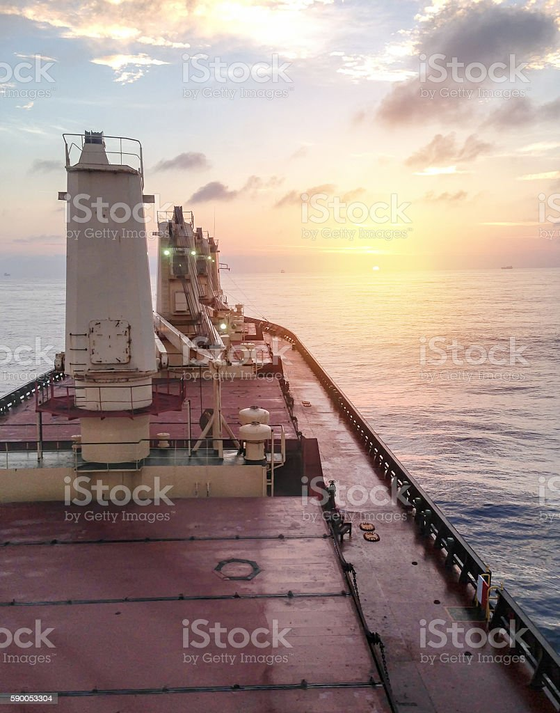 General cargo ship argosy in ocean at sunrise morning stock photo