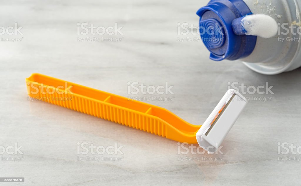 Generic disposable razor with empty can of foam stock photo