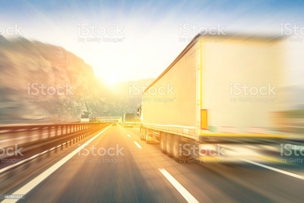 Generic semi trucks speeding on the highway at sunset stock photo