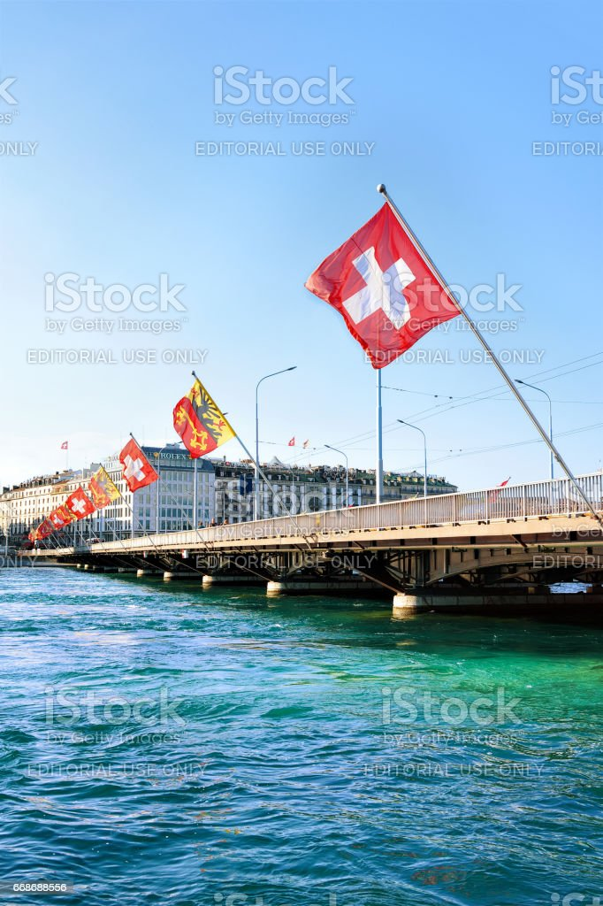 Geneva Lake and Mont Blanc bridge with many Swiss flags stock photo