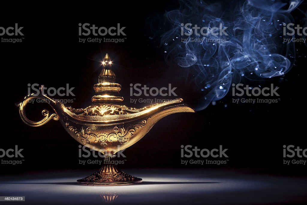 Genie's lamp under a spotlight with smoke coming out stock photo
