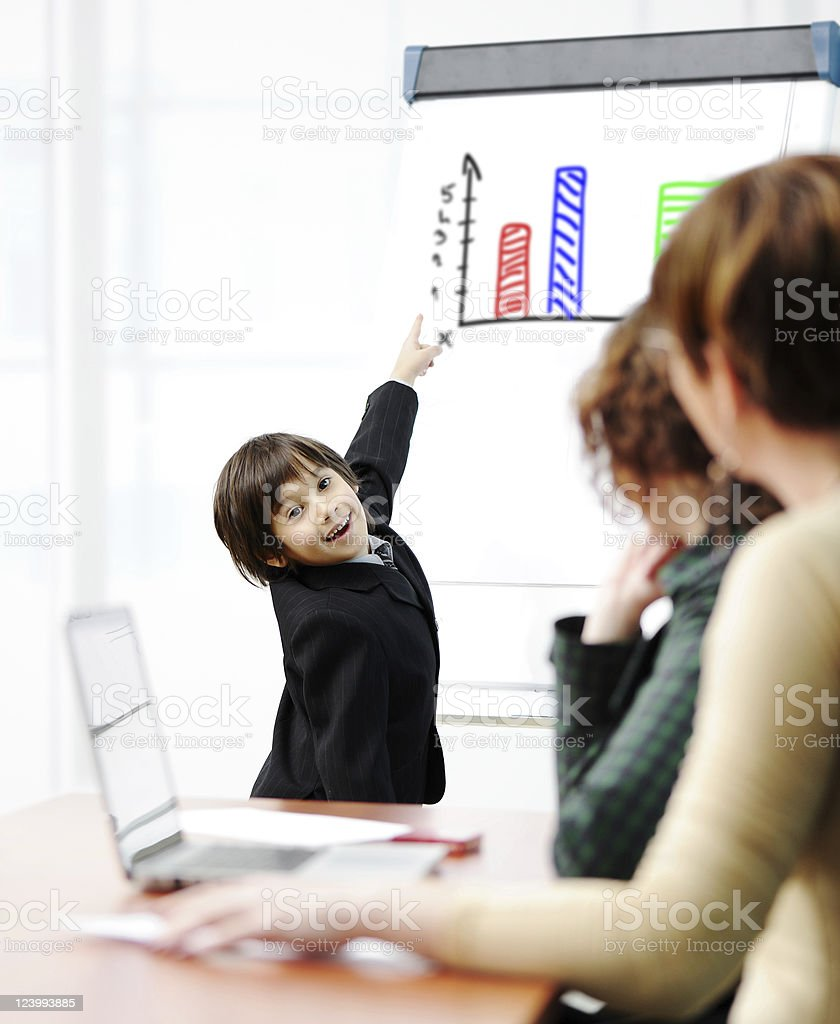 Genius kid on business presentation speaking to adults royalty-free stock photo