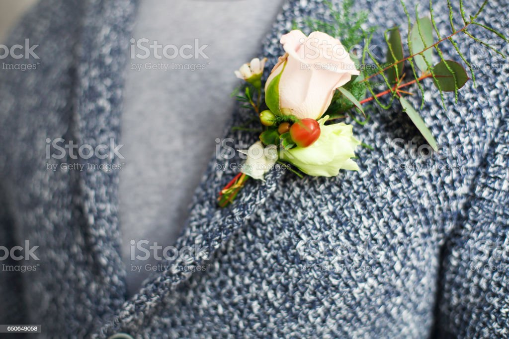 Gentle groom boutonniere with roses and beads stock photo