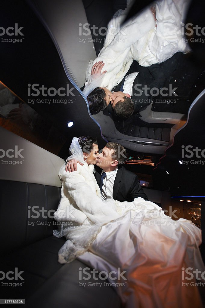Gentle kiss bride and groom in wedding limo royalty-free stock photo