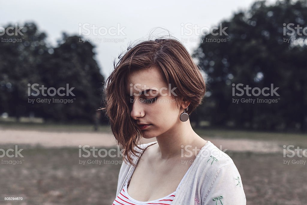 Gentle portrait of a sad girl outdoors stock photo