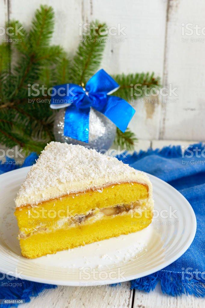 Gentle sponge cake with creamy banana layer, sprinkle coconut stock photo