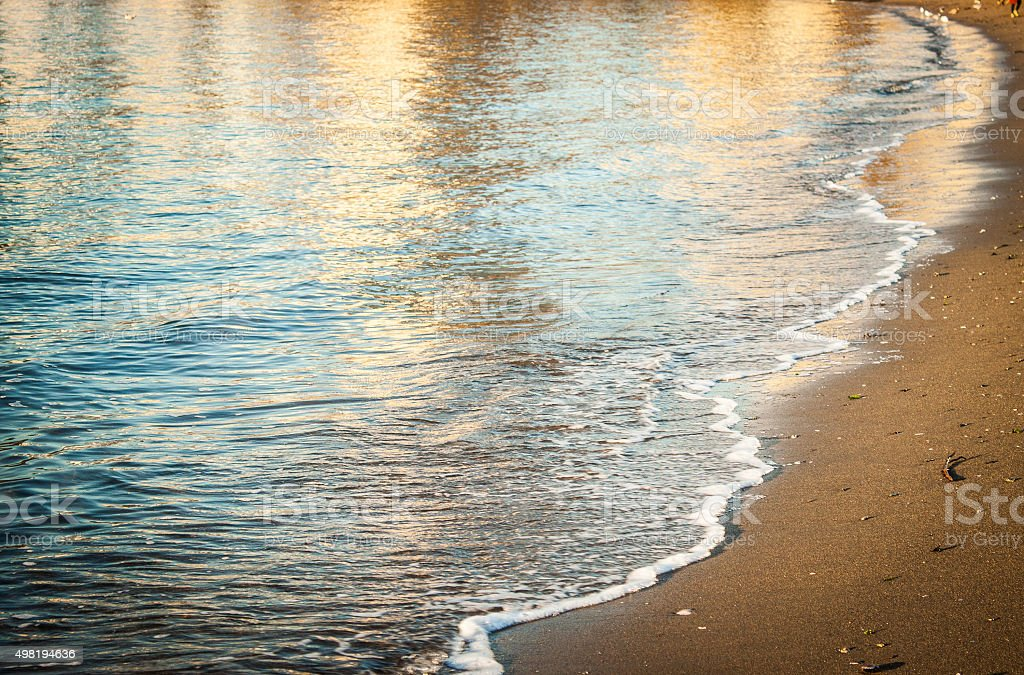 Gentle Waves Beachside with Reflections stock photo