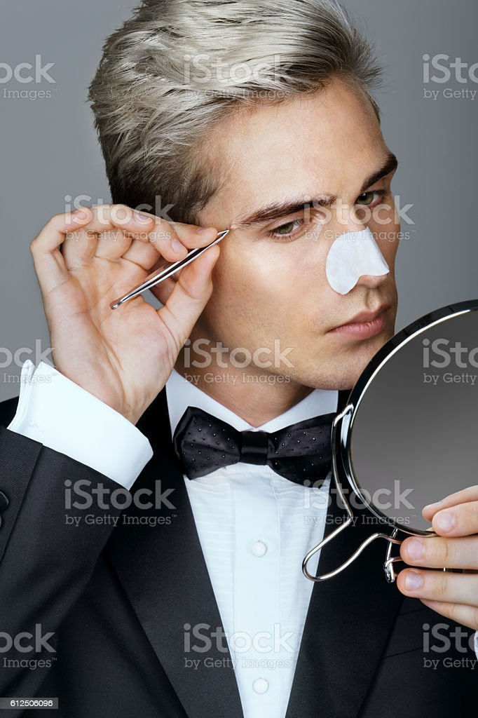 Gentleman concentrating on tweezing his eyebrows. stock photo
