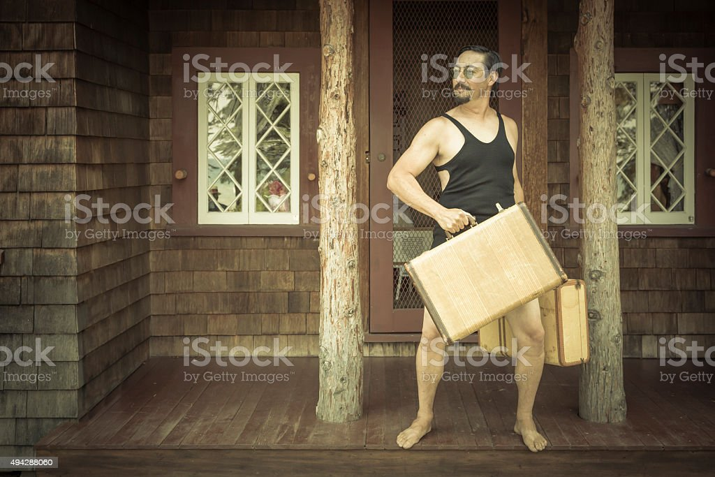Gentleman Dressed in 1920€™s Swimsuit Holds Suitcase on Porch stock photo