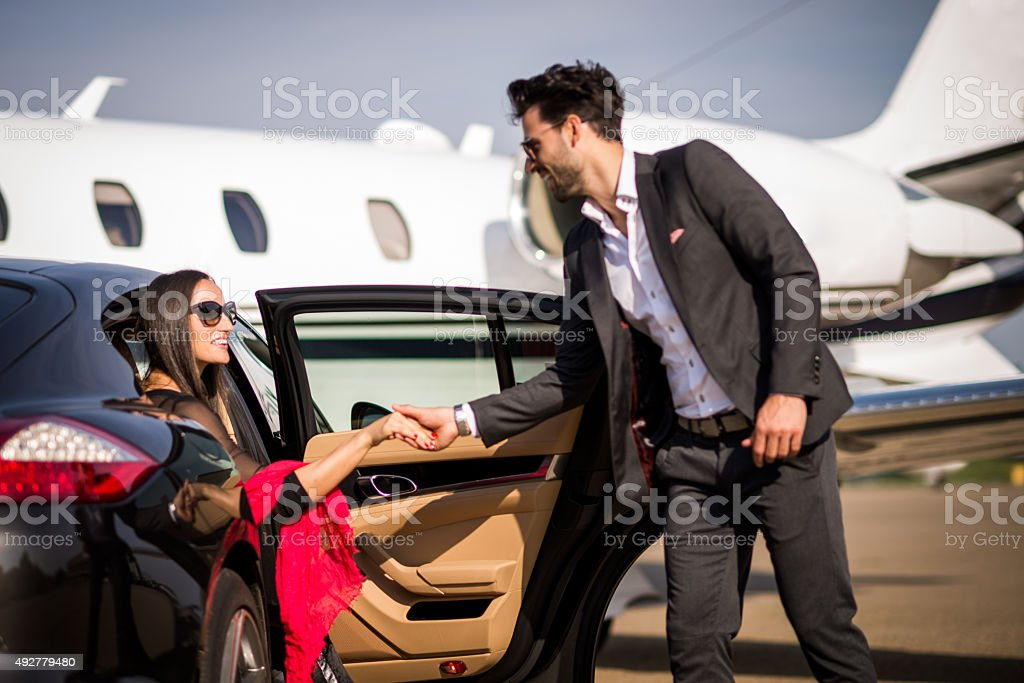 Gentleman helping woman to exit the vehicle stock photo