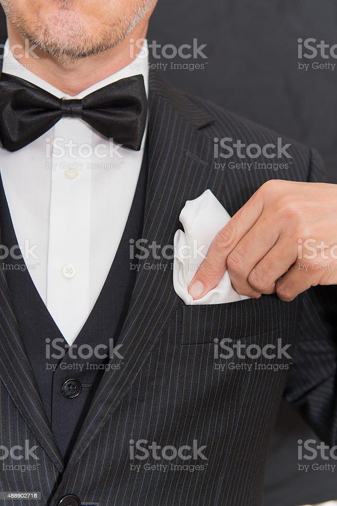 Gentleman In Black Tie Fixes Pocket Square, Vertical stock photo
