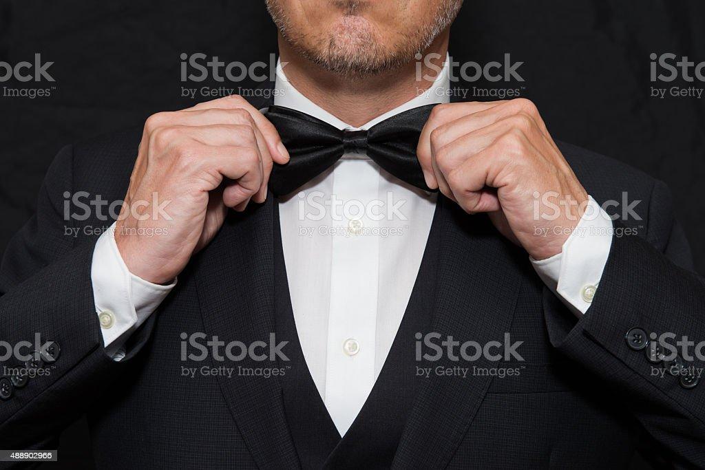 Gentleman in Black Tie Straightens His Bowtie stock photo