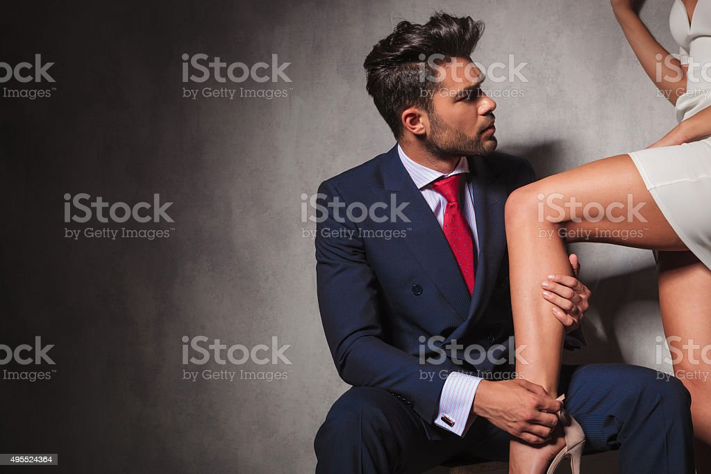 gentleman is helping his woman to get her shoes on stock photo