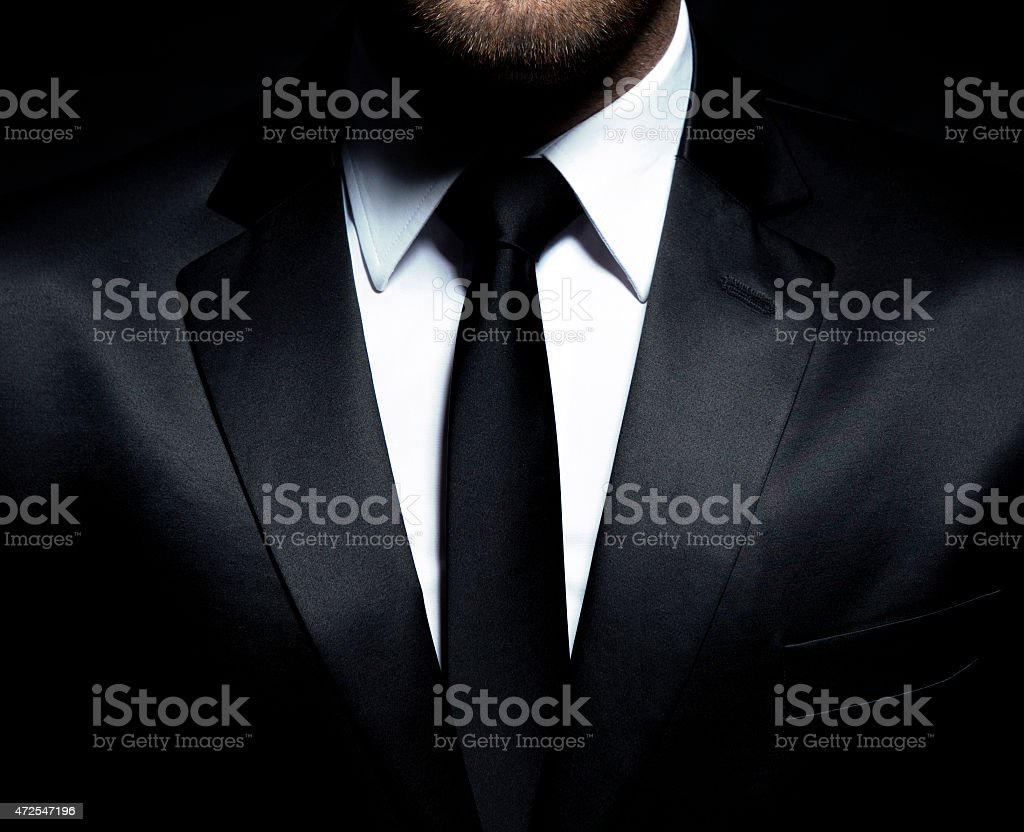 Gentleman wearing a black suit, shirt and tie, tuxedo stock photo