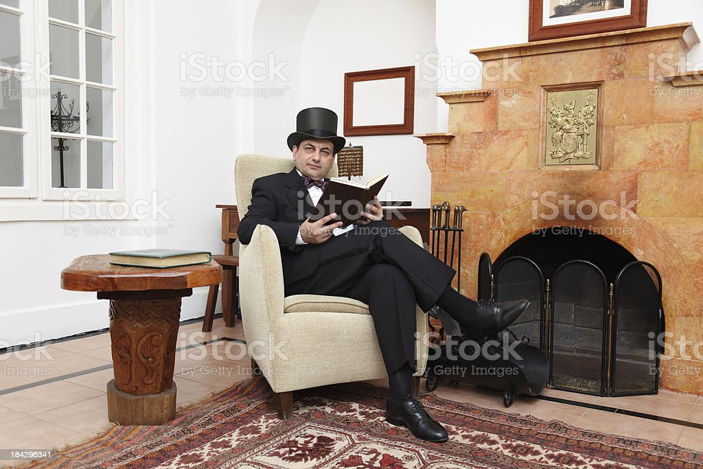 Gentleman with a book sits in armchair near fireplace stock photo
