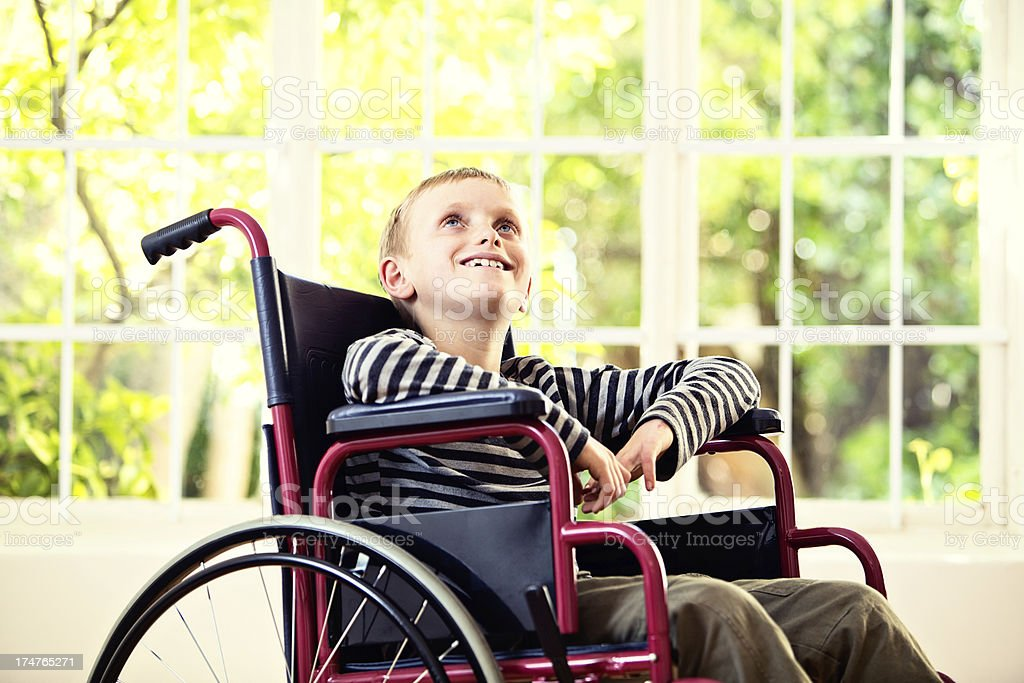 Gently smiling little boy in wheelchair next to window stock photo