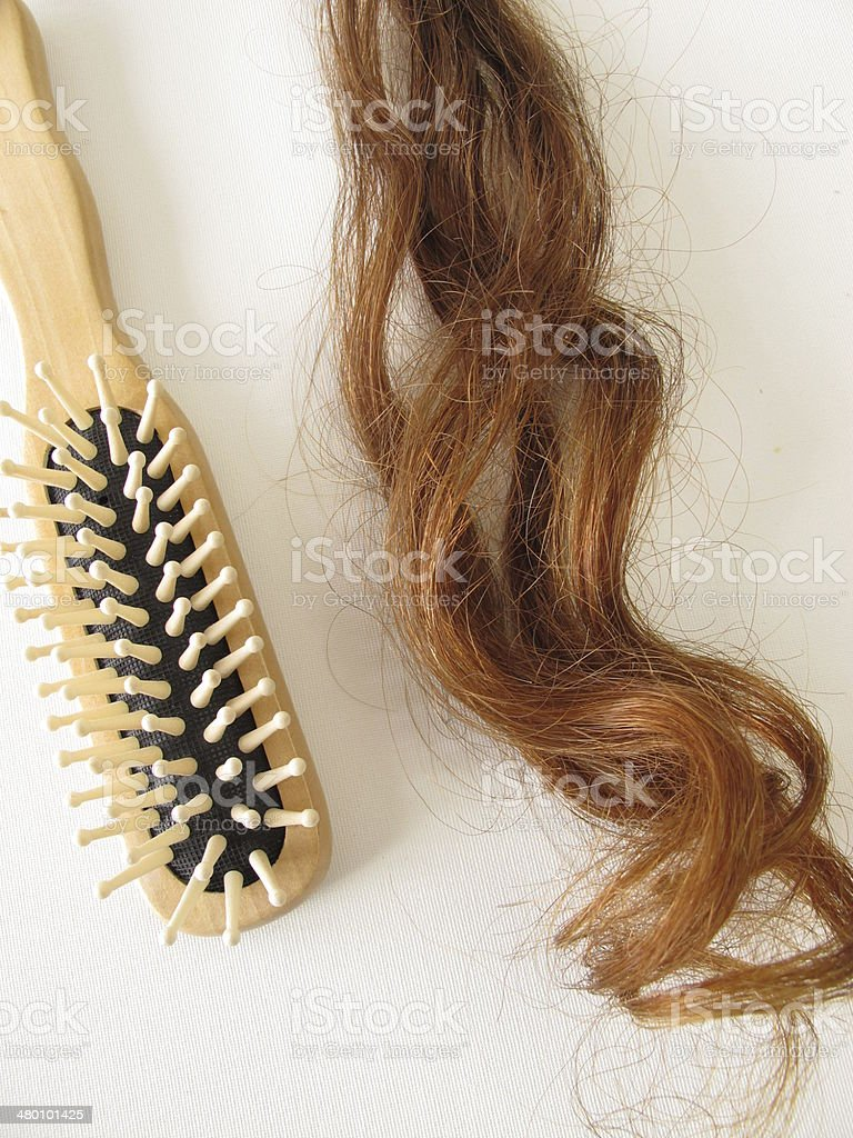 Genuine auburn hair strand and a hairbrush stock photo